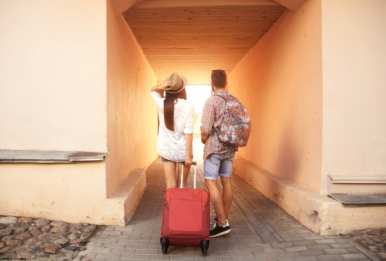 Two travelers on vacation walking around city with luggage
