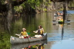 Group of adults and children canoeing on the river at Shingle Creek Regional Park in Kissimmee, Florida, in springtime.